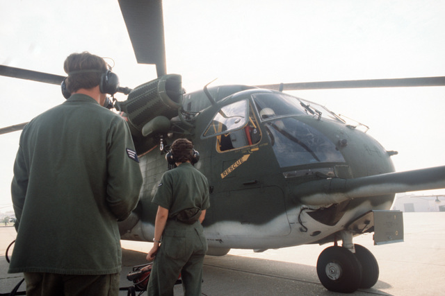Ground crewmen stand by with fire fighting equipment as a pilot does a preflight inspection of a 39th Aerospace Rescue and Recovery Wing HH-53 helicopter prior to flying to Woodbridge, England