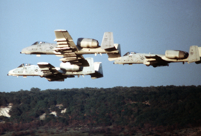 A ground-to-air left side view of three A-10A Thunderbolt II aircraft in low-level formation during a firepower demonstration for President Carter. The aircraft are assigned to the 355th Tactical Fighter Wing