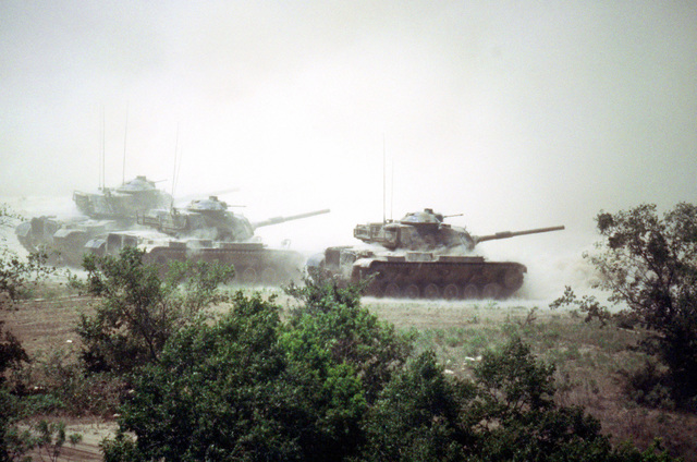 M-60A1 main battle tanks maneuver on the firing range during a mock assault conducted as part of a firepower demonstration for President Carter