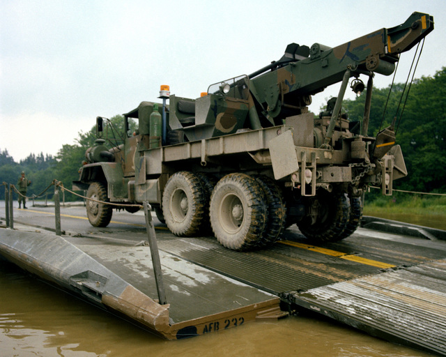 A 5-ton truck is driven across a ribbon bridge constructed by members of the 1457th Engineers, who were instructed by members of the 502nd Engineer Amphibious Floating Bridge Company during Reforger training exercises at the 7th Army Training Command