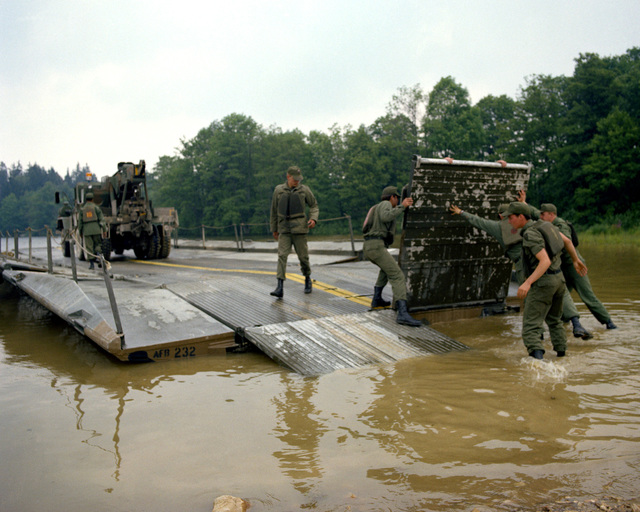 A ribbon bridge is assembled by members of the 1457th Engineer Battalion during Reforger training exercises at the 7th Army Training Command