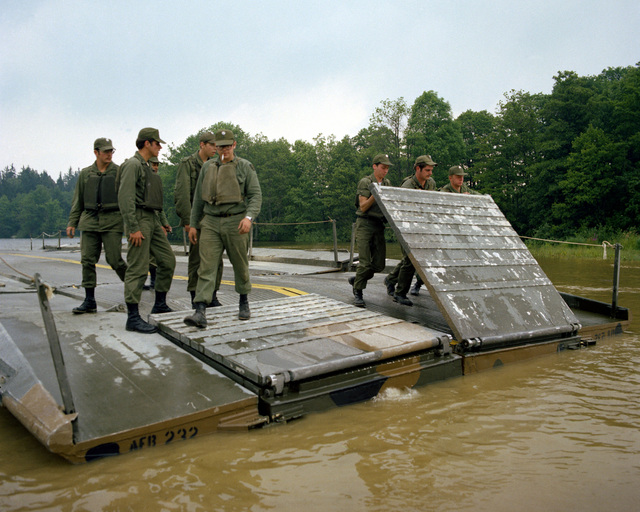 A ribbon bridge is assembled by members of the 1457th Engineering Battalion during Reforger training exercises at the 7th Army Training Command
