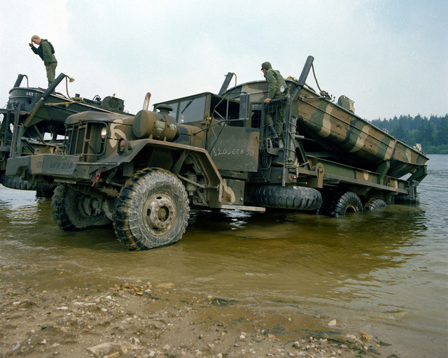 A ribbon bridge is launched from a 5-ton vehicle by members of the 1457th Engineering Battalion during Reforger training exercises at the 7th Army Training Command