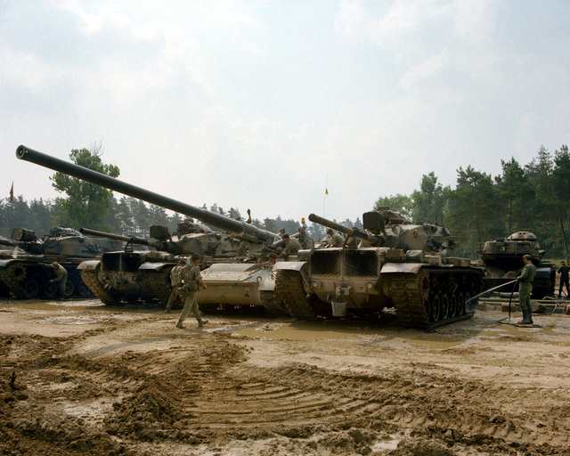 Members of Co. A, 4th Bn., 73rd Armor, wash M-60 tanks and a British 175mm self-propelled artillery (SPA) at the wash rack during Reforger training exercises at the 7th Army Training Command