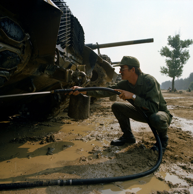 SPC 4 Daniel Kocher, Co. A, 4th Bn., 73rd Armor, uses a hose to wash mud off an M-60 tank during Reforger training exercises at the 7th Army Training Command