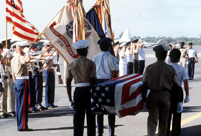 A combined services Color Guard stands at attention as pallbearers carry the flag draped casket of a former Missing In Action (MIA) person from a C-141 Starlifter aircraft to a waiting bus during a ceremony on the flight line. Fifteen former American MIAs from Southeast Asia are arriving at the base for positive identification by the Army Central Identification Laboratory