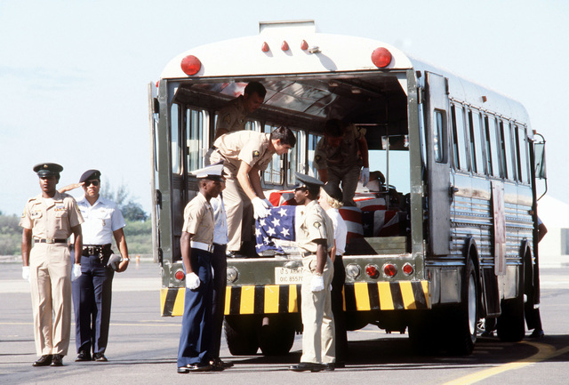 Combined services pallbearers place the flag draped casket of a former Missing In Action (MIA) person into a bus during a ceremony on the flight line. Fifteen former American MIAs from Southeast Asia are arriving at the base for positive identification by the Army Central Identification Laboratory