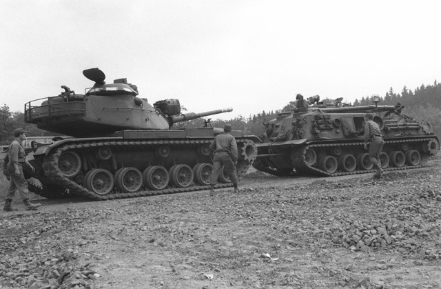 A right front view of an M-88 armored recoery vehicle towing an M-60 main battle tank from a storage shelter in preparation for Exercise REFORGER 78