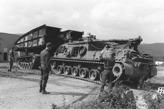 A right side view of an M-88 armored recovery vehicle towing an Armored Vehicle Launched Bridge (AVLB) from storage as preparations are made for Exercise REFORGER 78