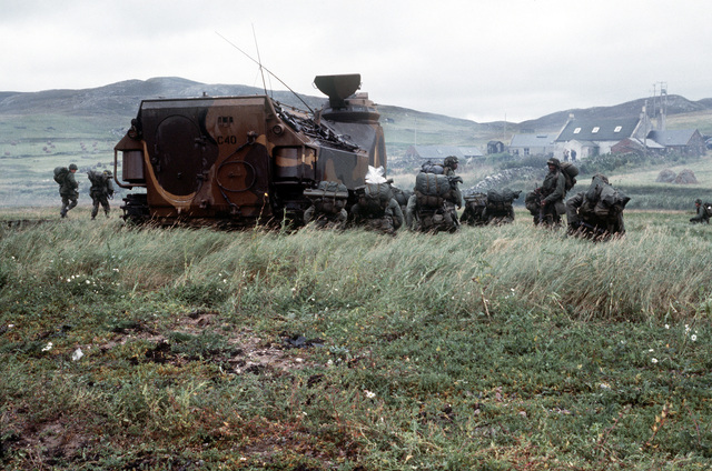 A squad of Marines from the 4th Marine Amphibious Brigade is given a briefing. Next to them is an LVTP-7 tracked landing vehicle. The 4th MAU is participating in the NATO exercise Northern Wedding