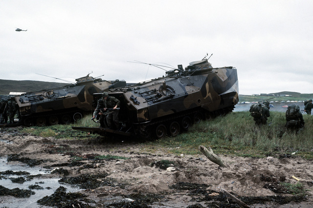 Combat-ready Marines debark from two LVTP-7 tracked landing vehicles on Red Beach during a NATO exercise. The 4th Marine Amphibious Brigade is participating in the NATO exercise Northern Wedding