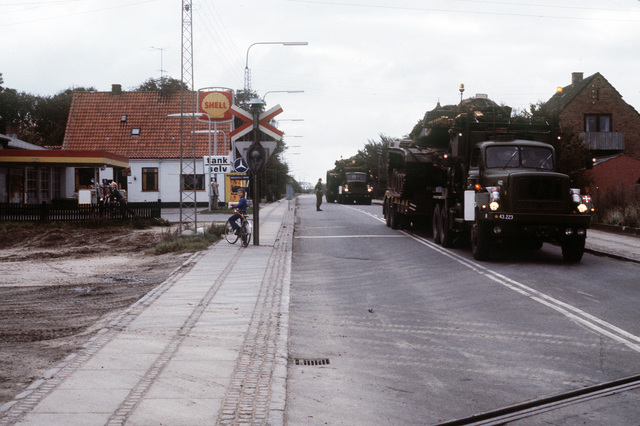Denmark trucks carry U.S. Marine M-60A1 tanks to the railroad yard for transportation to Eutin, West Germany. The 4th Marine Amphibious Brigade is participating in the NATO exercise Northern Wedding