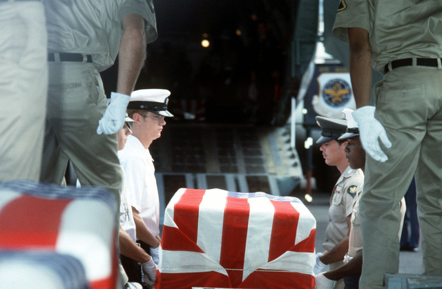Combined services pallbearers transfer the flag draped casket of a former Missing In Action (MIA) person from a bus to the C-141 Starlifter aircraft during a ceremony on the flight line. Eleven former MIAs returned from Vietnam are being airlifted to Travis Air Force Base, California
