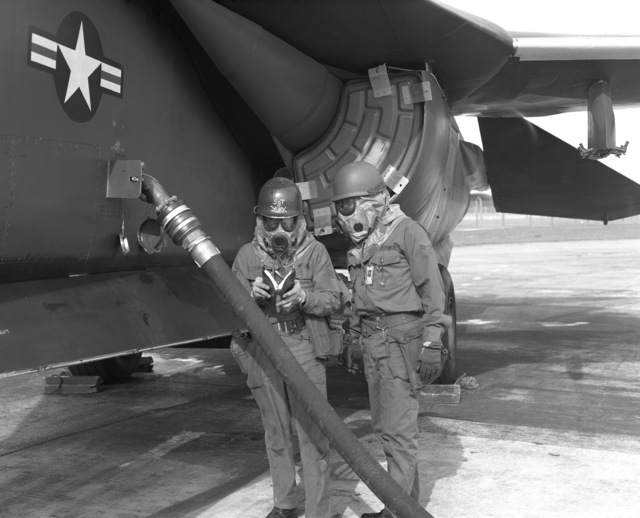 Sergeant Patrick York, crew chief, and AIRMAN First Class Jeffrey F. Hall (right), both of the 48th Organizational Maintenance Squadron, consult a manual while refueling an F-111 aircraft under simulated fallout conditions