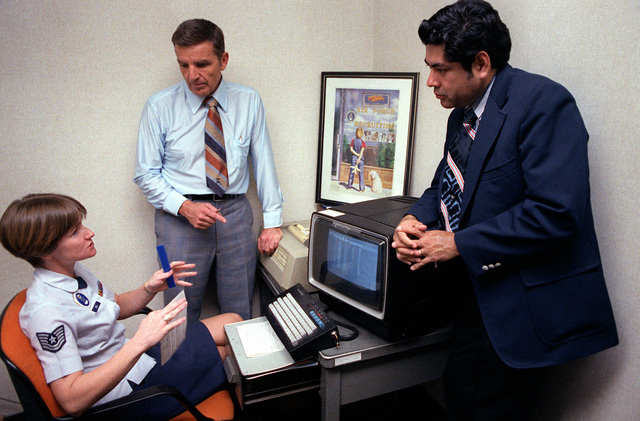 A recruiter talks with Personnel Research psychologist Dr. Joe H. Ward and Mathematician Manuel Pina, left to right, in the San Antonio Induction Center. The recruiter is seated at the visual display terminal of a job bank computer system. Ward and Pina, Brooks Air Force Base Human Resources Laboratory, designed a part of the system, which matches jobs and applicant's fields