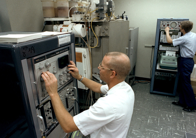 Radiation Measurement Technician TSGT James Messenger, foreground, calibrates the autogamma radiation counting system and the automated gamma spectrometer at the Radiation Science Laboratory. 2LT Jeffrey Triebel, background, checks background radiation with the instrument panel prior to running radiation sample analysis