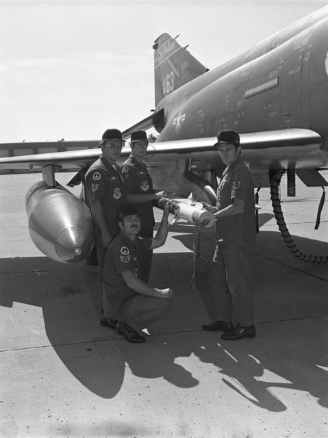 """U.S. Air Force weapons load team assigned to the 119th Fighter Wing""""Happy Hooligans"""", North Dakota Air National Guard, pose for a photo with a AIM-9 Sidewinder air-to-air missile, attached to a F-4D Phantom II aircraft, during the 1978 William Tell""""Weapons Competition at Tyndall, Air Force Base, Fla. Pictured standing from left to right, TECH. SGT. Gerald Kuehl; STAFF SGT. James Kram; TECH. SGT. Phillip Poe and kneeling STAFF SGT. Gene Henderson. (A3604) (U.S. Air Force PHOTO) (Released)"""