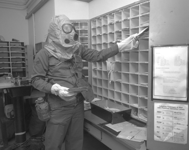 AIRMAN First Class Harry Leonard, postal clerk, sorts mail while wearing nuclear-biological-chemical gear during a test to evaluate his unit's ability to perform under fallout conditions