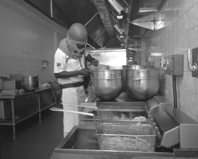 Sergeant Bill Starks, 513th Tactical Airlift Wind Food Service, checks the beef stew through his protective hood while participating in a test to evaluate his unit's ability to perform under fallout conditions
