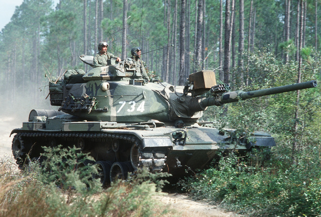 Members of the 24th Infantry Division maneuver an M60A1 main battle tank during Exercise GALLANT EAGLE '79