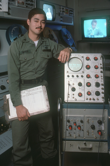 A US Army audiovisual technician stands beside test equipment inside a television studio