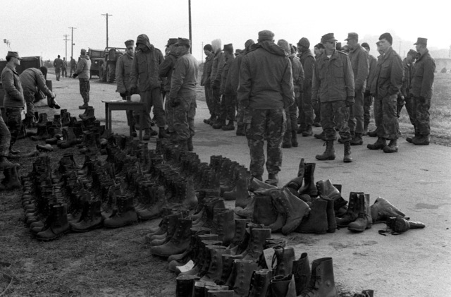 Marines from the 1ST Marine Air Wing who are taking part in the Marine amphibious unit landing exercise, receive cold weather boots as part of their cold weather clothing