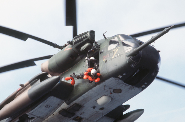 """A litter carrying a """"survivor"""" is hoisted aboard a hovering HH-53 helicopter from the 55th Aerospace Rescue and Recovery Squadron, Eglin AFB, Florida. The sea rescue exercise is being staged for a movie production"""