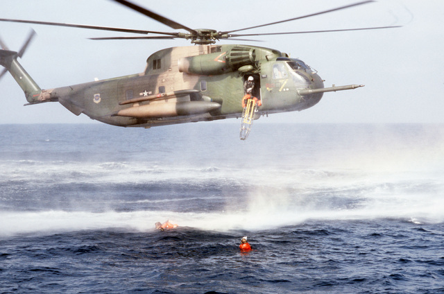"""A litter is dropped from a hovering HH-53 helicopter to pararescuemen of the 55th Aerospace Rescue and Recovery Squadron, Eglin AFB, Florida, as they assist a """"survivor"""" floating in the water. The sea rescue exercise is being staged for a movie production"""