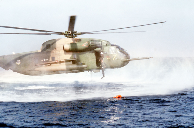 """An HH-53 helicopter hovers low over the water as a pararescueman of the 55th Aerospace Rescue and Recovery Squadron, Eglin AFB, FL, jumps in to assist a """"survivor"""". The sea rescue is being staged for a movie production"""