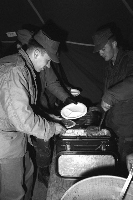 Kang Nung Air Services. Lance CPL. Unrinie from 1ST Marine Air Wing (1ST MAW), serves beef stew to SGT. Dulian of Marine Air Base Squadron 12, during a Marine amphibious unit landing exercise