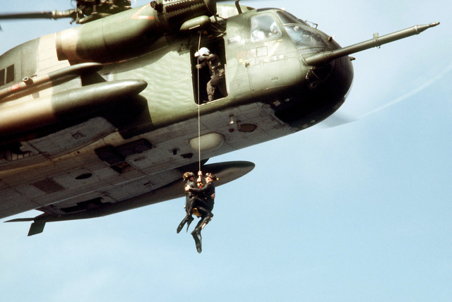 """Pararescuemen of the 55th Aerospace Rescue and Recovery Squadron, Eglin AFB, Florida, are hoisted aboard a hovering HH-53 helicopter after recovering a """"survivor"""" from the water. The sea rescue exercise is being staged for a movie production"""