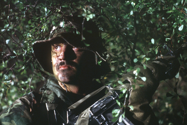 "STAFF Sergeant Dave Drake of the 55th Aerospace Rescue and Recovery Squadron, conceals himself in the underbrush while searching for a ""downed"" pilot. The night rescue exercise is being staged for a movie production"