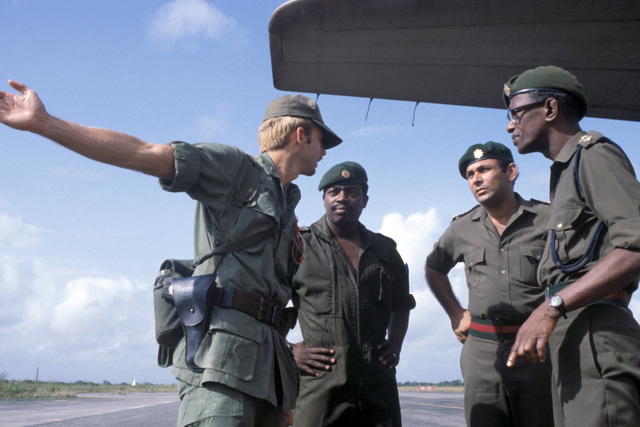 A member of a US Army medical team meets with Guyanese officials upon his arrival to assist with the humanitarian relief efforts following the Jonestown tragedy