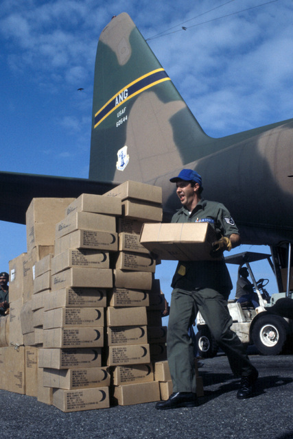 A staff sergeant from Howard Air Force Base, Canal Zone, carries cases of C-rations from a C-130 Hercules aircraft for use by US military personnel participating in humanitarian relief efforts following the Jonestown tragedy