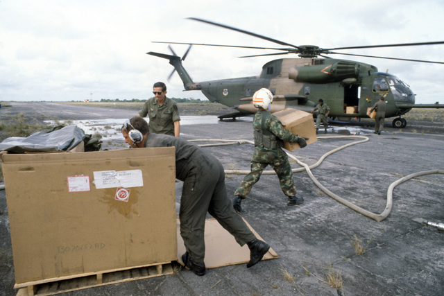 Colonel (COL) Bruce M. Durvine, vice commander of the 39th Aerospace Rescue and Recovery Wing, and members of the 55th Aerospace Rescue and Recovery Squadron carry boxes of plastic body bags to an HH-53 Jolly Green Giant helicopter for use in the evacuation of bodies from Jonestown