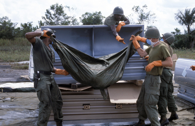 US military personnel place a body bag containing the remains of a victim of the Jonestown tragedy in a coffin for transport to Dover Air Force Base, Delaware
