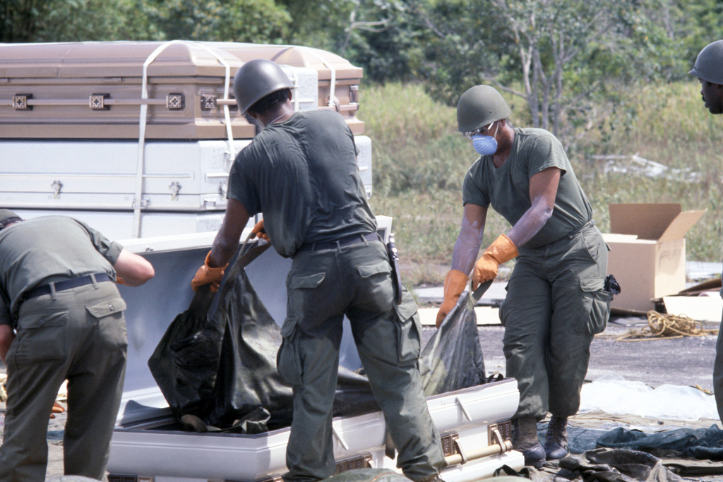 US military personnel place a body bag containing the remains of the  victims of the Jonestown tragedy in a coffin for transport to Dover Air  Force Base, Delaware - PICRYL Public Domain