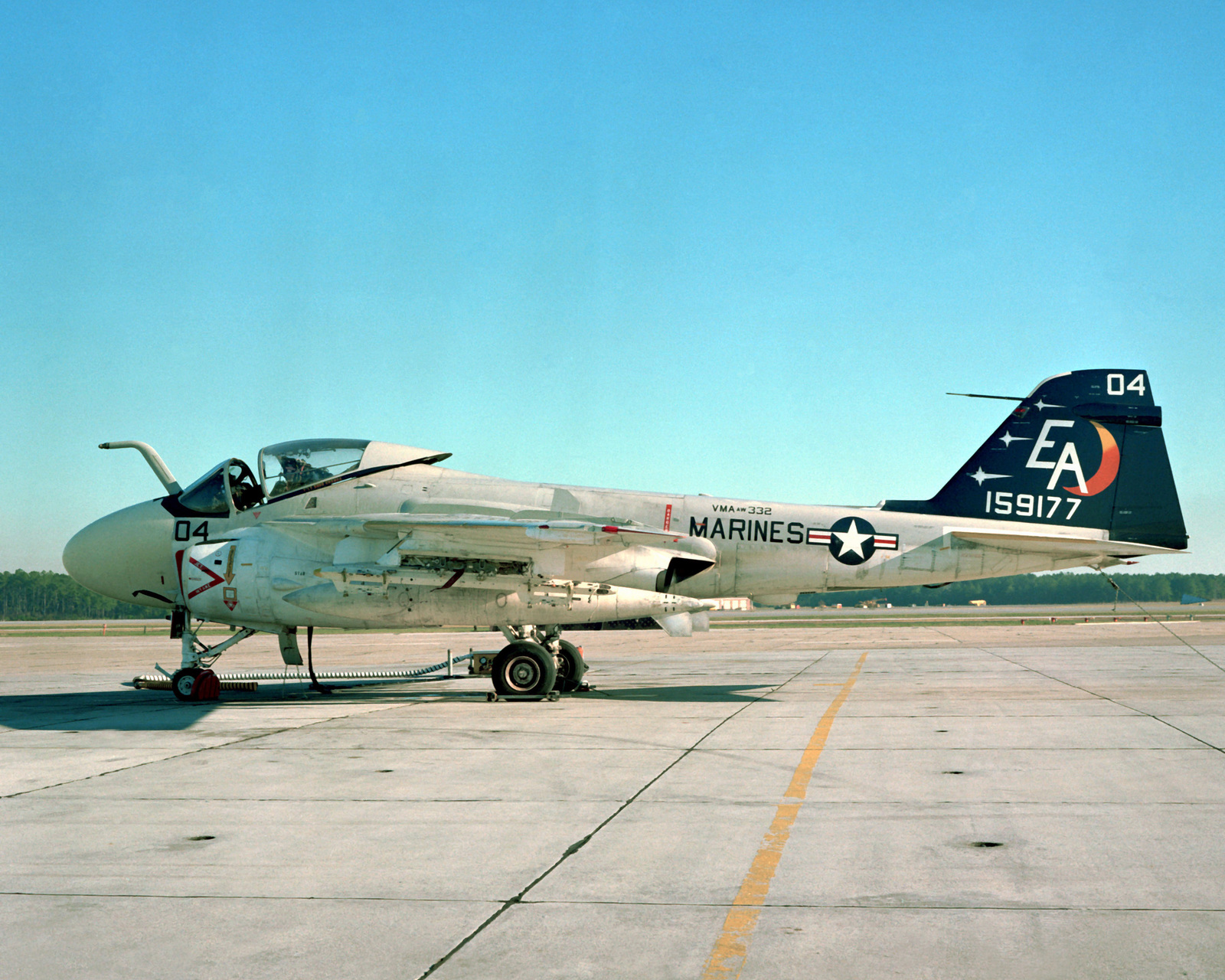 A left side view of a Marine A-6E Intruder aircraft sitting on the flight line. The Intruder is from Marine All-Weather Medium Attack Squadron 332 (VMAWF-332)
