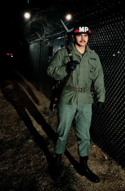 A US Army military policeman patrols a fence line
