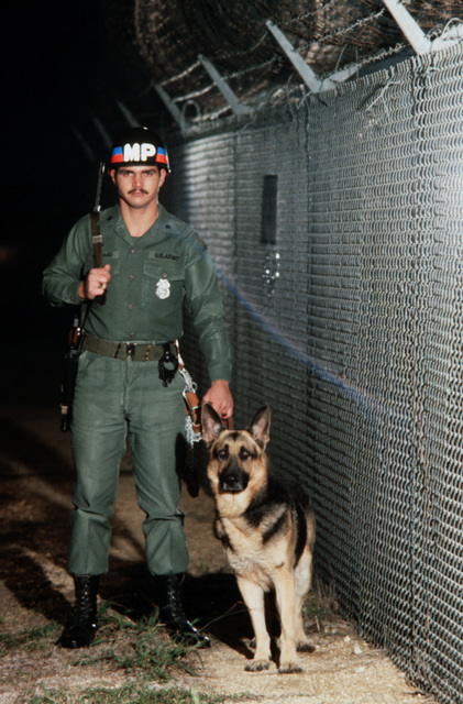 A US Army military policeman patrols a fence line with a patrol dog