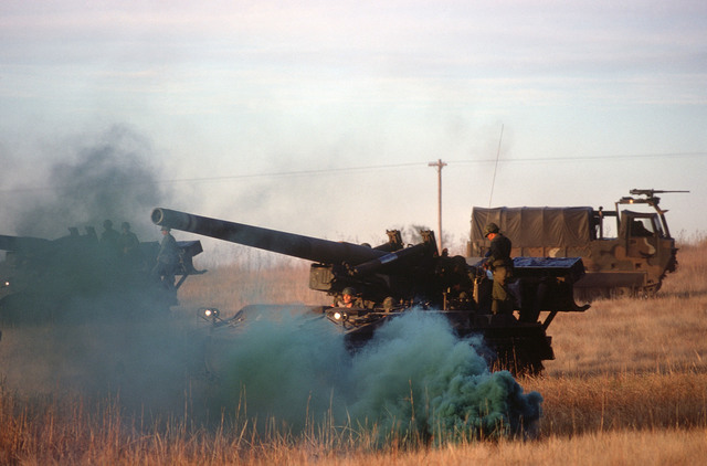 An M110 203 mm self-propelled howitzer is hidden by smoke during a training exercise. An M548 tracked cargo carrier is in the background