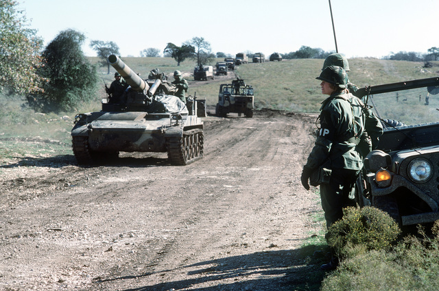 U.S. Army military policemen observe an M-110 203mm howitzer passing by with a convoy of other vehicles