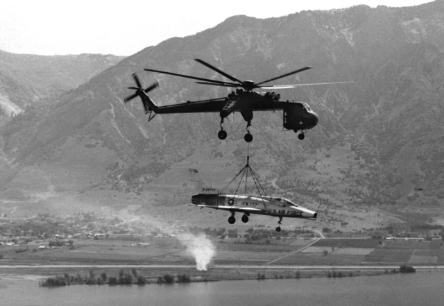 A CH-54 Flying Crane helicopter transports an F-100 Super Sabre aircraft on its last flight. The aircraft, from 388th Tactical Fighter Wing at Hill Air Force Base, Utah will be placed on static display near the headquarters building