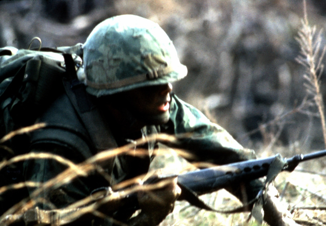 A combat-ready Marine cradles his M-16A1 rifle as he crawls through the mud during a field combat training exercise
