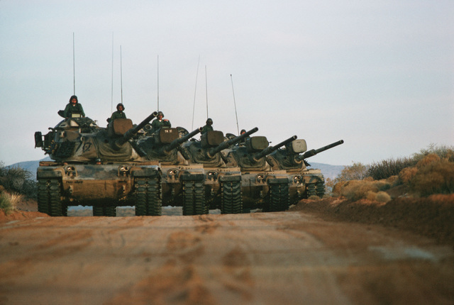 A convoy of M60 main battle tanks move down a road during a training exercise