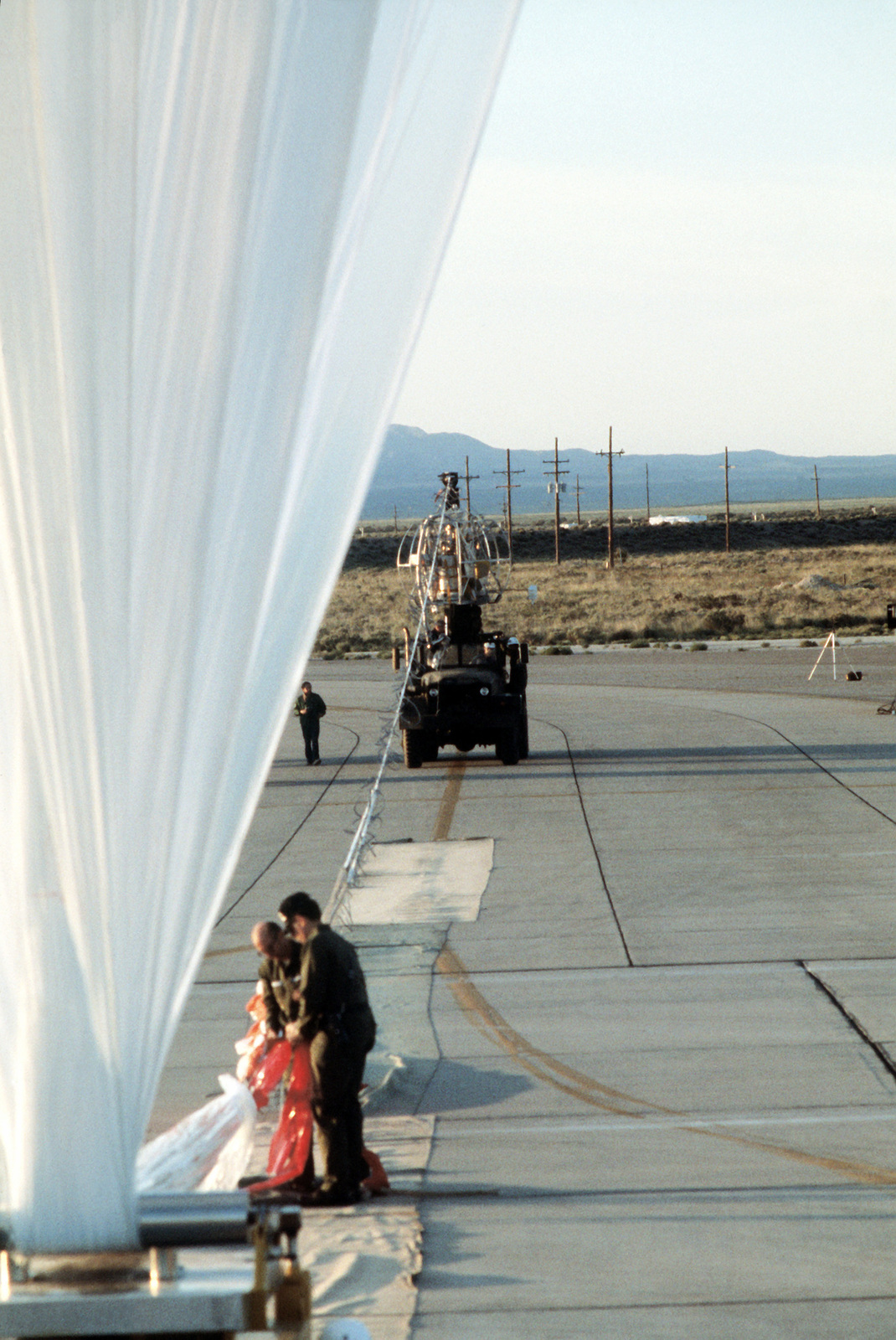 A helium-filled balloon is readied for lift-off by members of the Balloon Research and Development Test Branch, Air Force Geophysics Laboratory