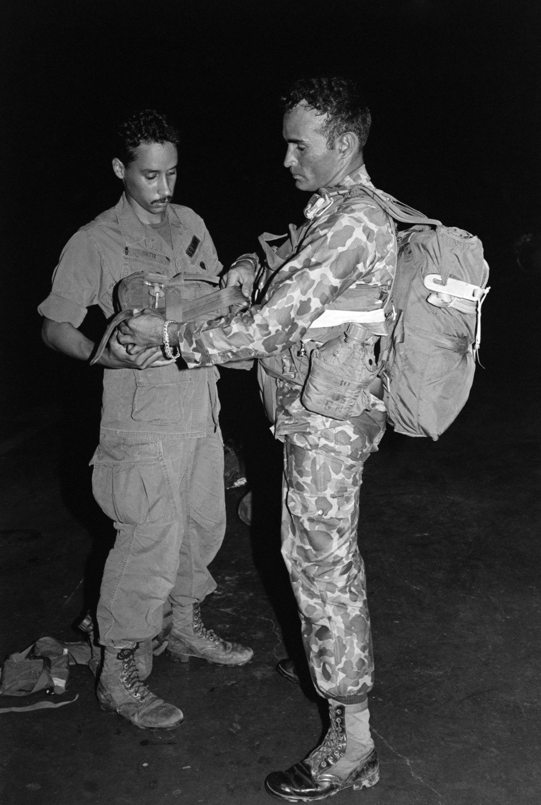 A member of Company A, 3rd Battalion, 5th Infantry, US Army, inspects the spare parachute worn by a soldier of the Panama National Guard piror to an airborne assault during a joint US/Panamanian exercise