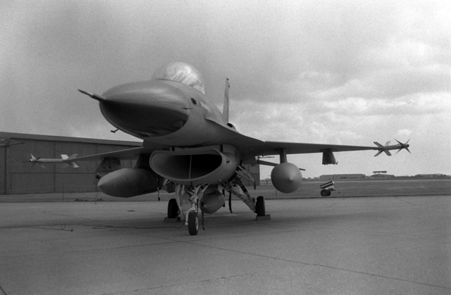 A view of a pre-production U.S. Air Force F-16 Fighting Falcon aircraft, as it sits on the flight line in front of a hangar. The aircraft is here for European tests and evaluations