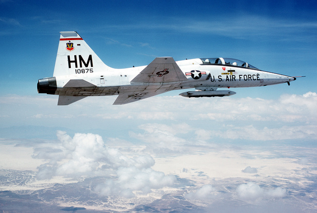 An air-to-air right side view of a T-38 Talon aircraft. The aircraft is equipped with a fuselage-mounted weapons pod