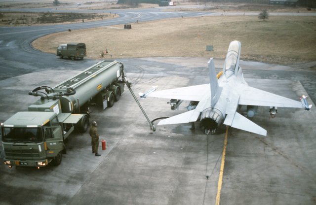 An F-16 Fighting Falcon aircraft is refueled on the flight line during a training exercise